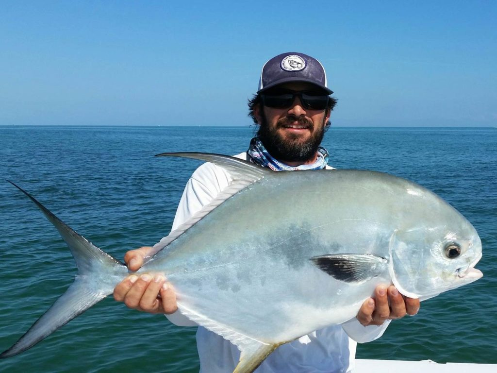 An angler holding a large Permit fish caught in the Florida Keys flats