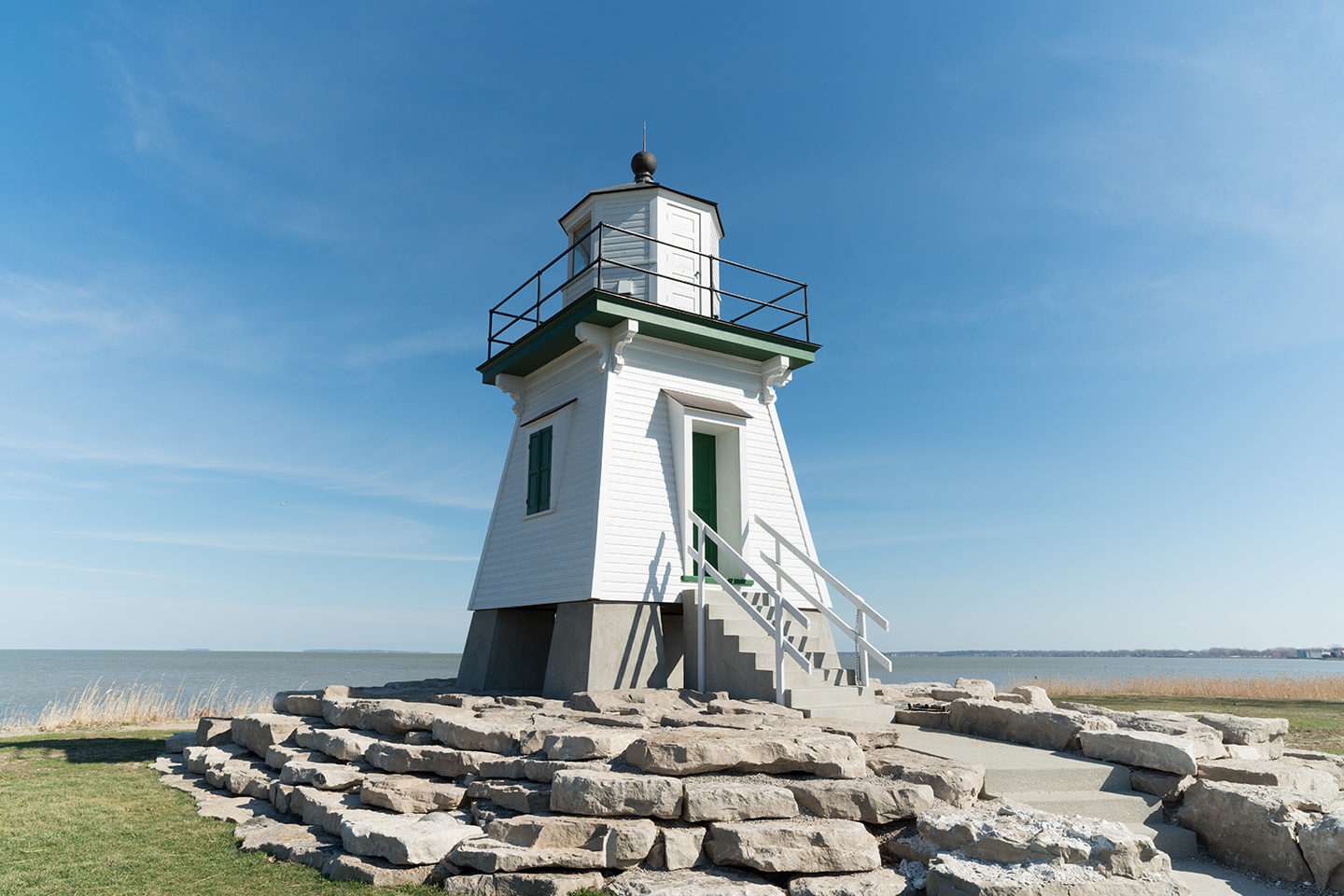 A white lighthouse in Port Clinton, one of the best summer fishing destinations on the Great Lakes, with the blue sky behind and green grass beneath it