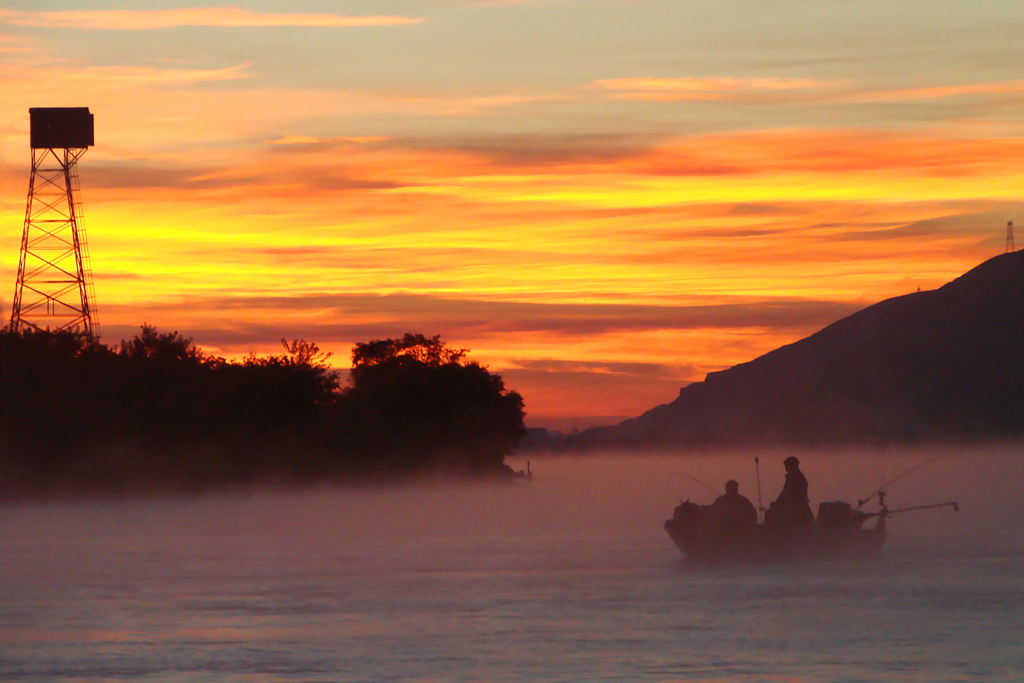 A charter boat trolls the Columbia River for Salmon at sunset