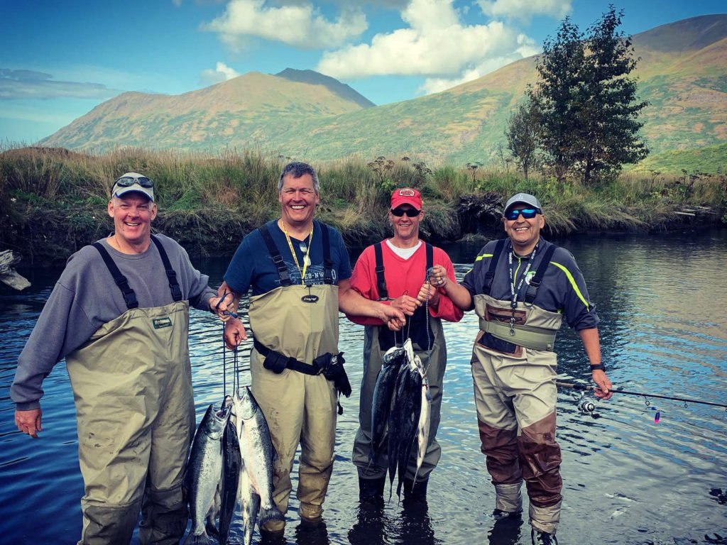 Four happy river anglers that have just caught a lot of Salmon in Alaska