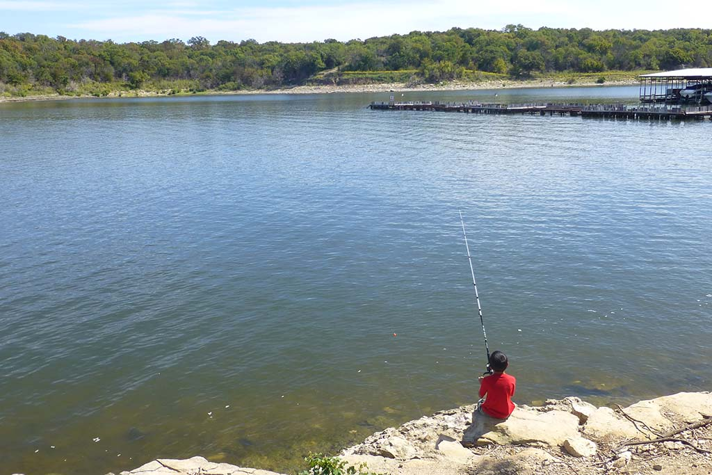 A boy shore fishes from Striper in Lake Texoma's Eisenhower Park