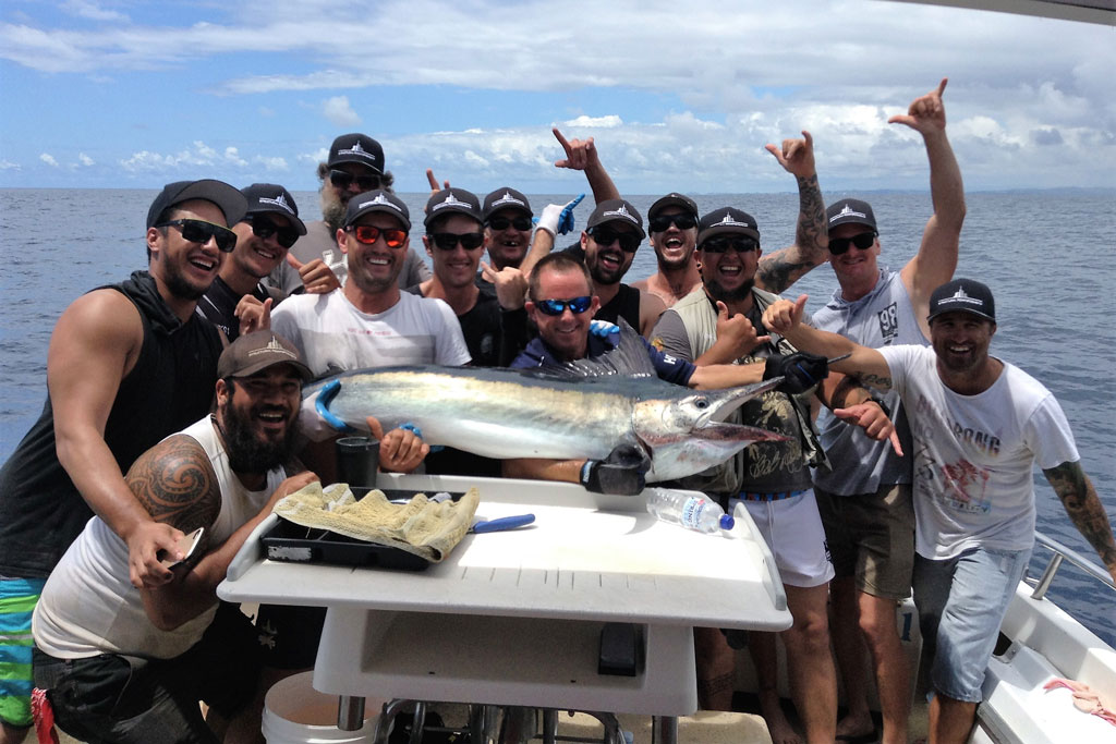 A group of anglers standing on a boat, holding a Black Marlin, with a table in front of them, and cloudy skies in the background
