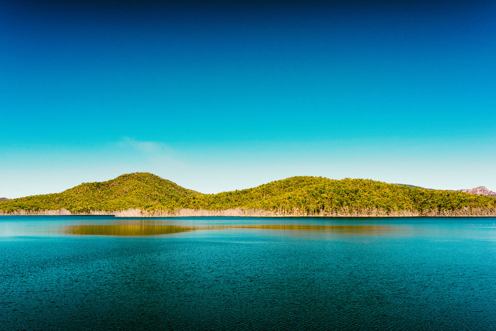 The view of green hills and calm water from the Hinze Dam