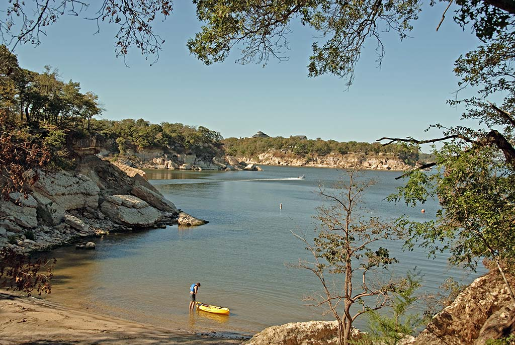 A view of Lake Texoma with greenery in the foreground, kayakers, and the lake itself