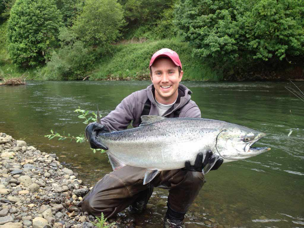 A man crouches holding a large Chinook Salmon in an Oregon river
