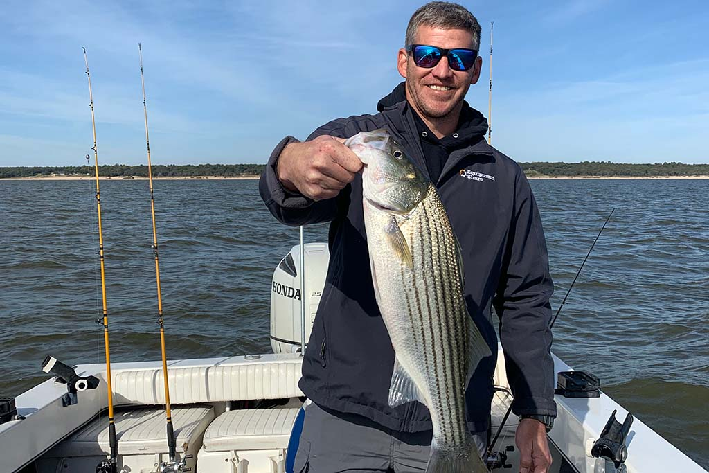 A smiling man stands aboard a charter boat holding a Striper in Lake Texoma