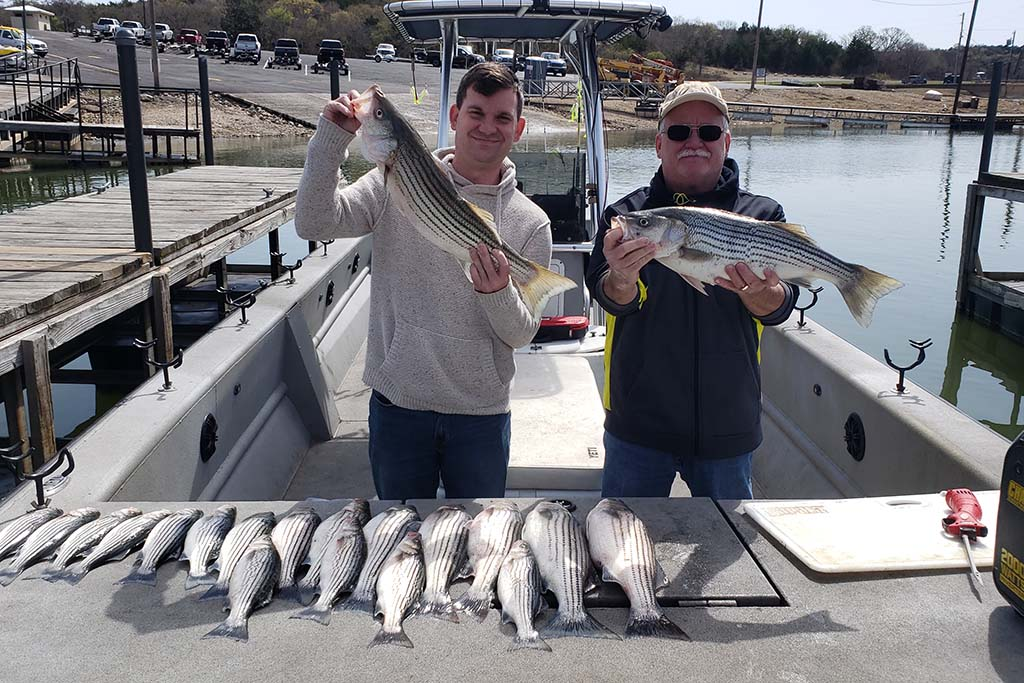 Two men stand aboard a docked Lake Texoma charter boat with lots of Stripers displayed