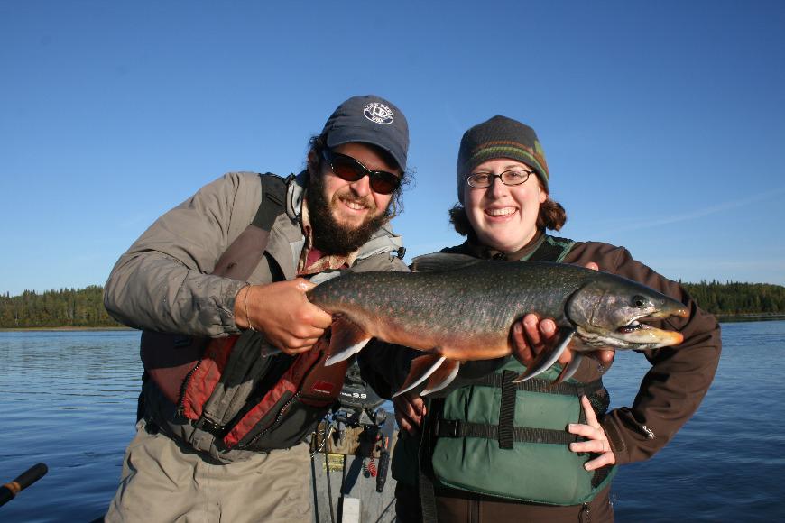 Two fishermen holding a Dolly Varden in Alaska