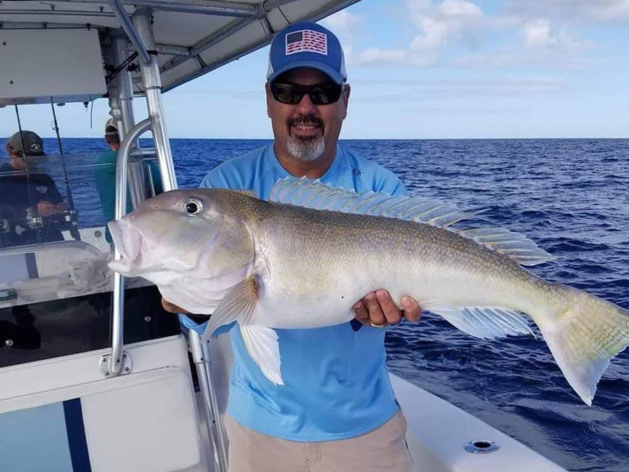 A smiling angler on a boat holding freshly caught Tilefish