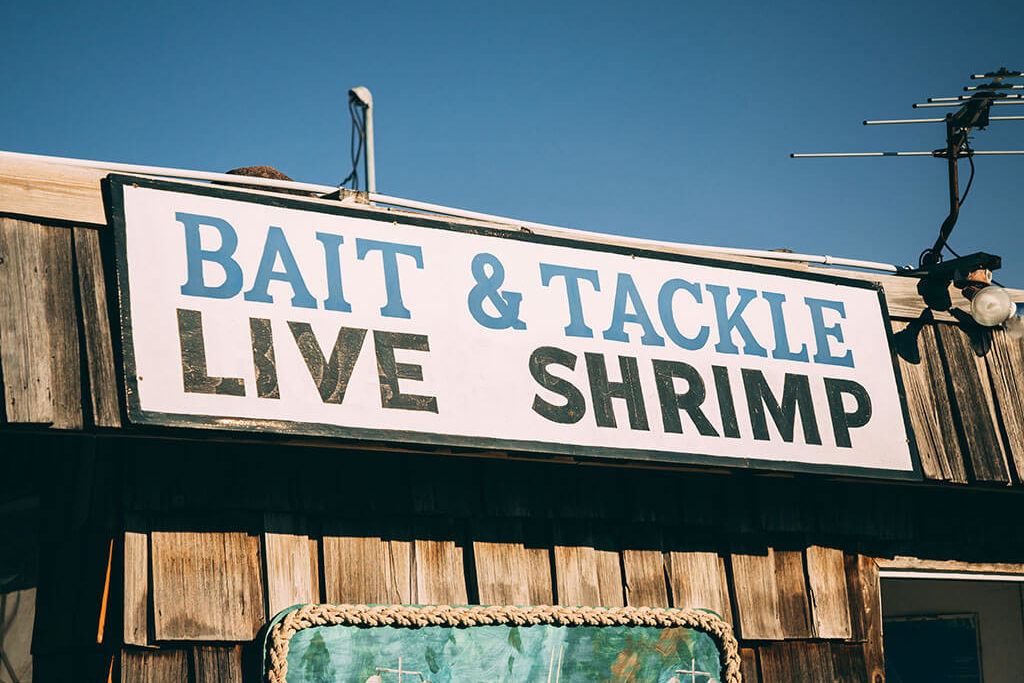 """A tackle shop with a large sign reading """"BAIT & TACKLE, LIVE SHRIMP"""""""