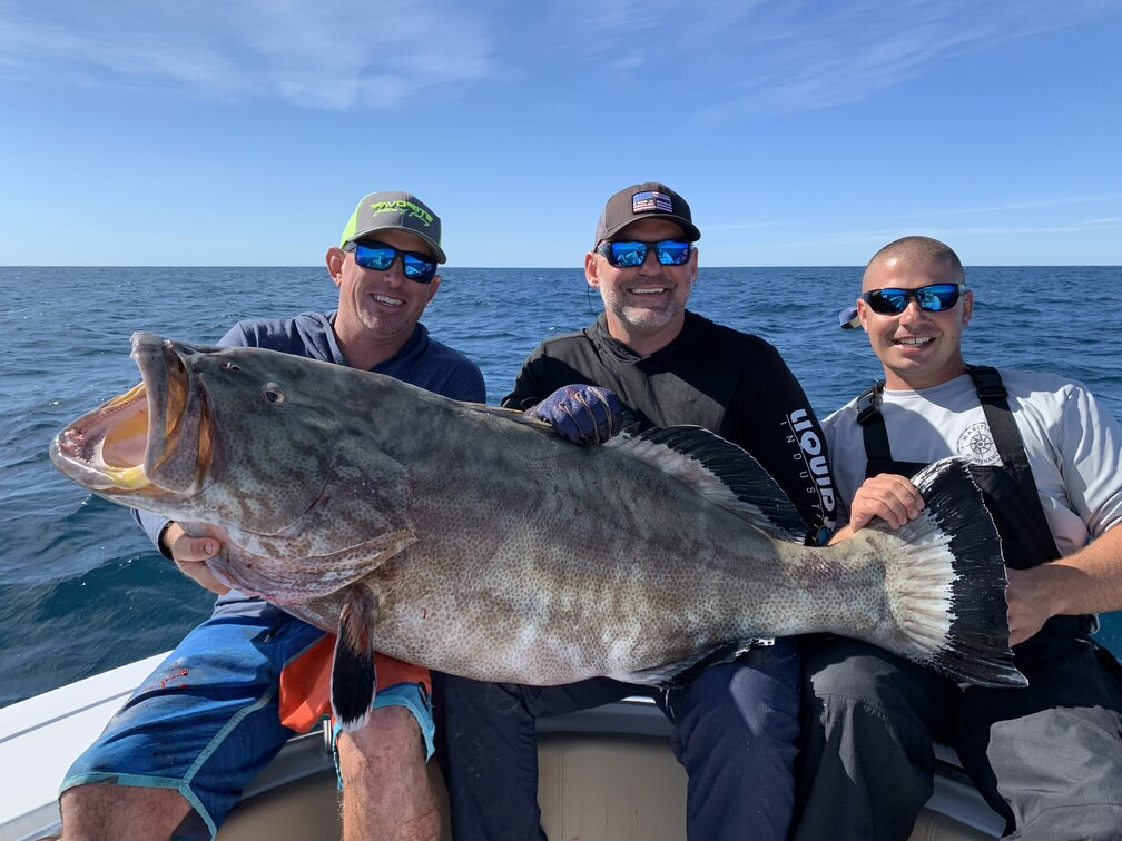 Three happy anglers on a fishing boat offshore holding a huge Black Grouper
