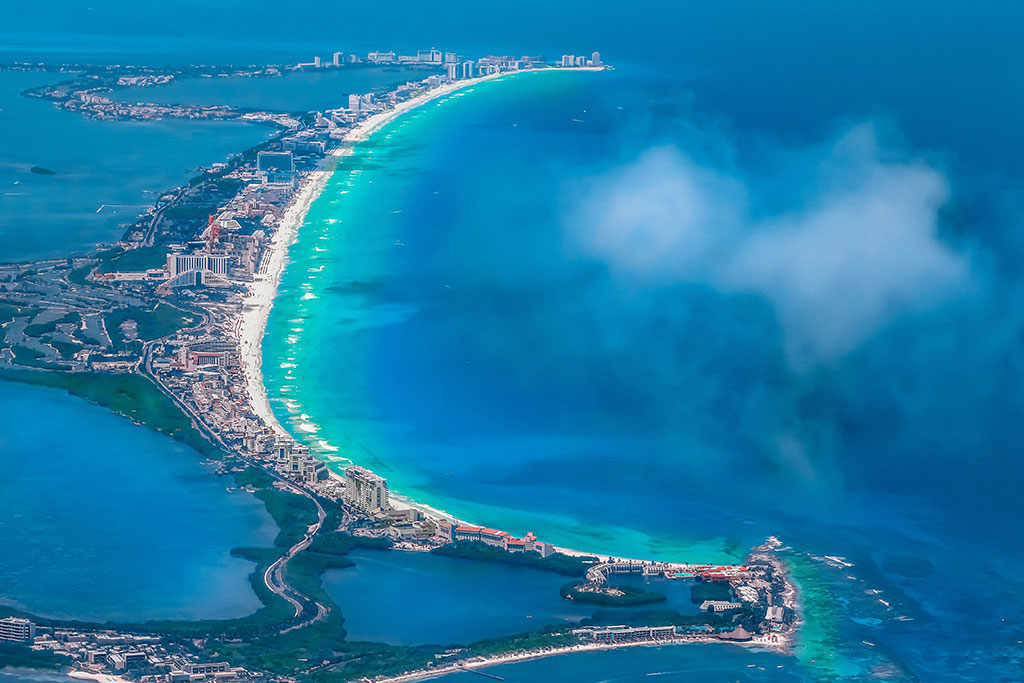 An aerial view of Cancún with a beach and the ocean on the right hand side and bays on the left