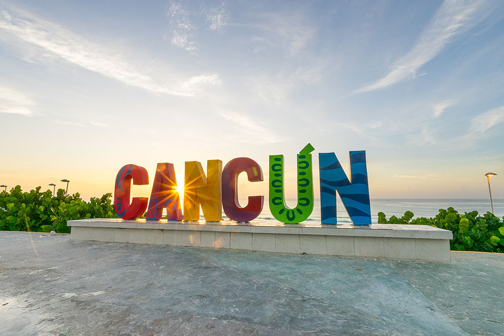 Coloured letters spell out Cancún as the sun sets behind the sea in the background