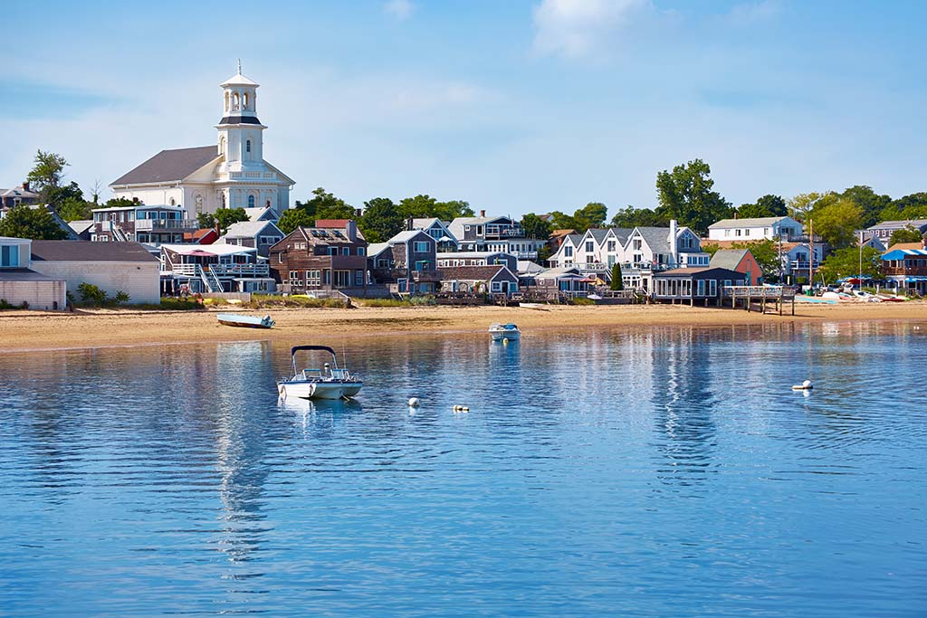 A view of a Cape Cod beach on a sunny day with the water in the foreground