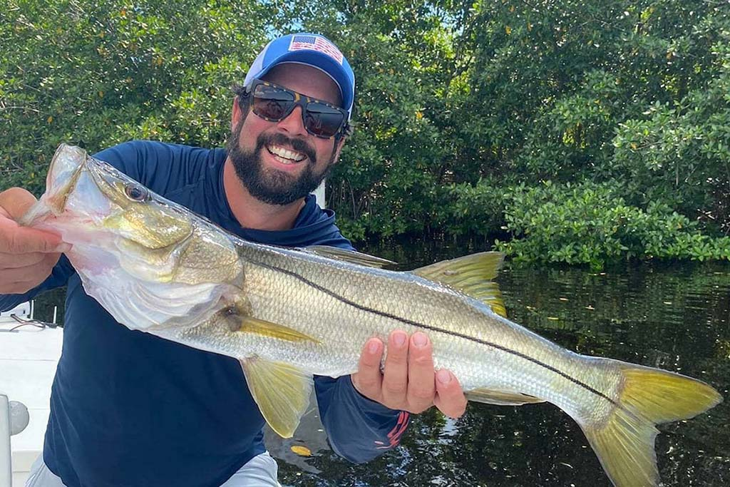 A man holds a Snook up to the camera with the Everglades' water and trees behind him