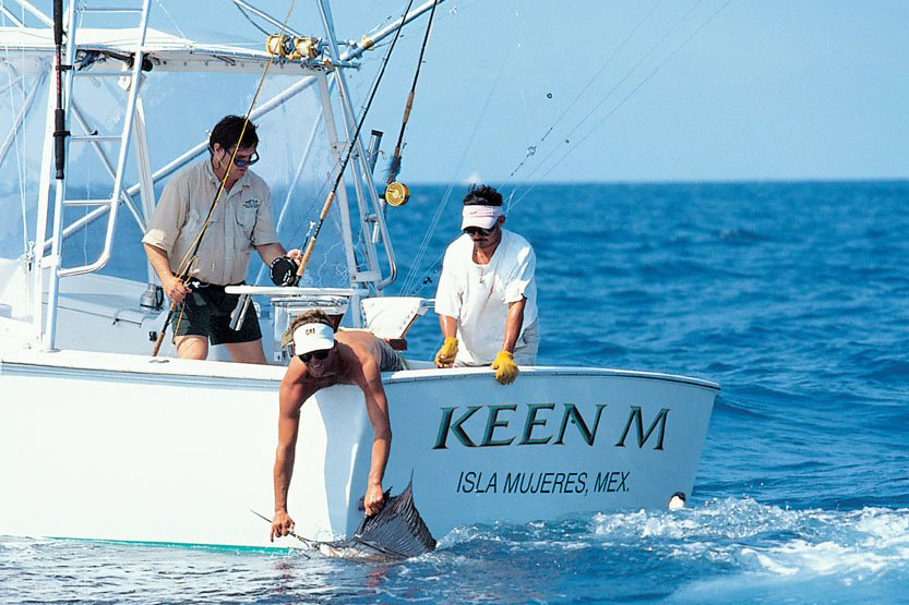 Three anglers aboard a boat, with one holding a Sailfish in the water by the bill and another holding a fly fishing line