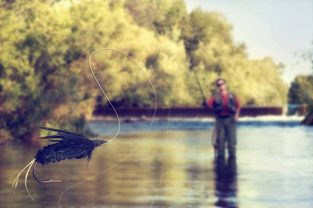 A man casts his line towards the camera with the water in the background and the fly in the foreground