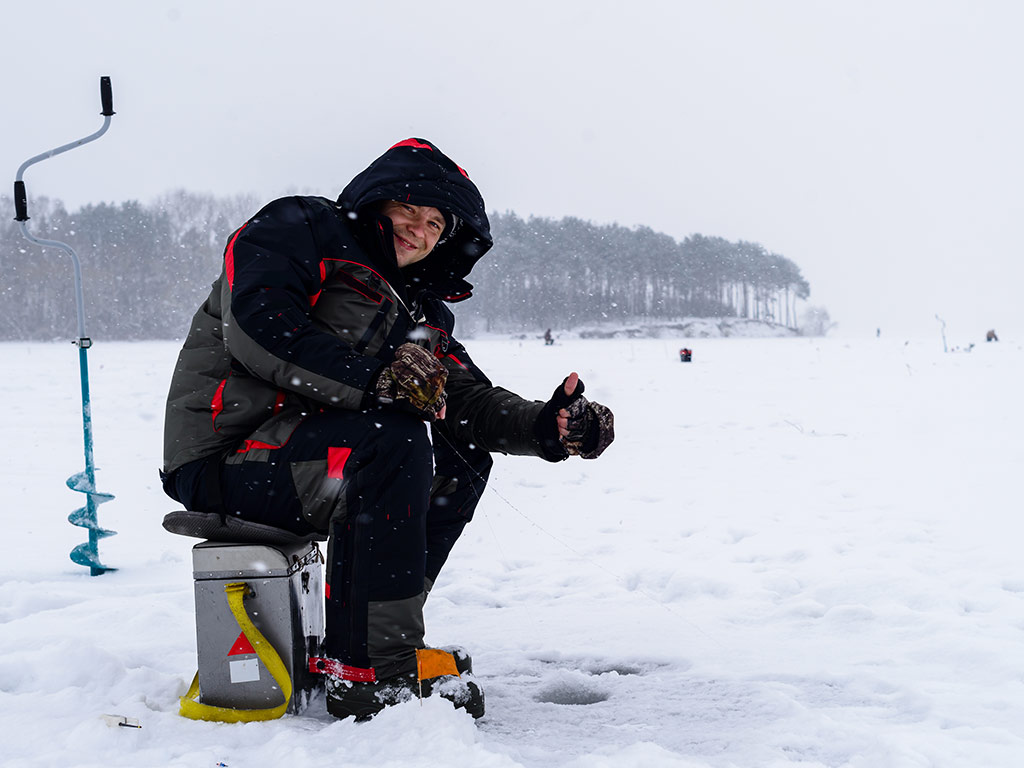 Angler sitting on a box and holding a thumbs up over a hole in the ice.