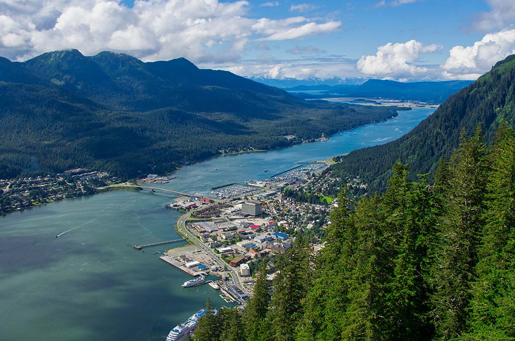 An aerial view of Juneau with the cityscape to the right and the mountains to the left with the water running through the middle