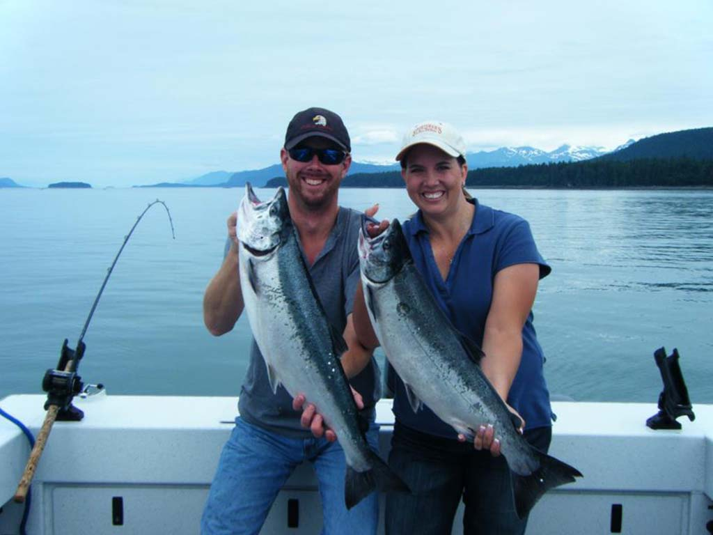 A man and woman stand on a charter boat holding large fish including a Salmon