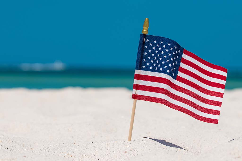 An American flag stuck in the sand at a beach on a sunny day with water in this distance