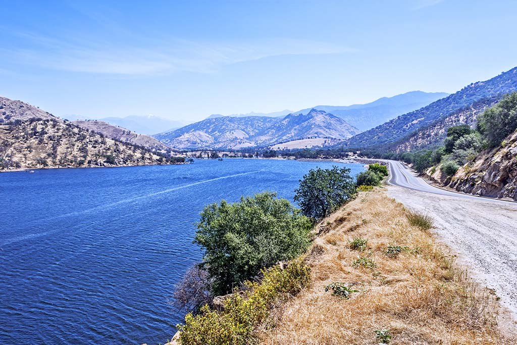 A view of Lake Kaweah on a sunny day with the mountains to the left and a path to the right