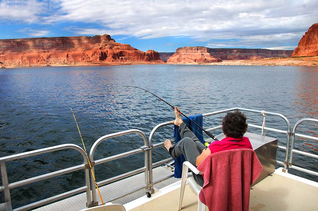A woman relaxes as she fishes from a dock on Lake Powell