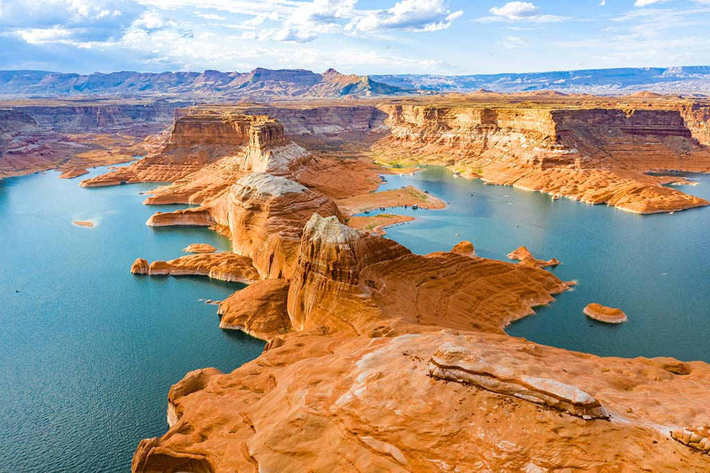 An aerial view of Lake Powell with red rocks and blue water on a sunny day