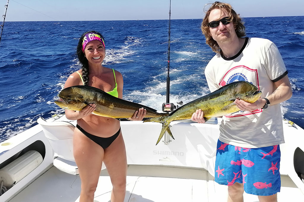 A male and female angler hold a Mahi Mahi each as a boat speeds offshore in Mexico