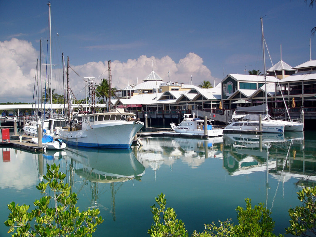The harbour in Port Douglas. Several boats are moored in front of the harbour building