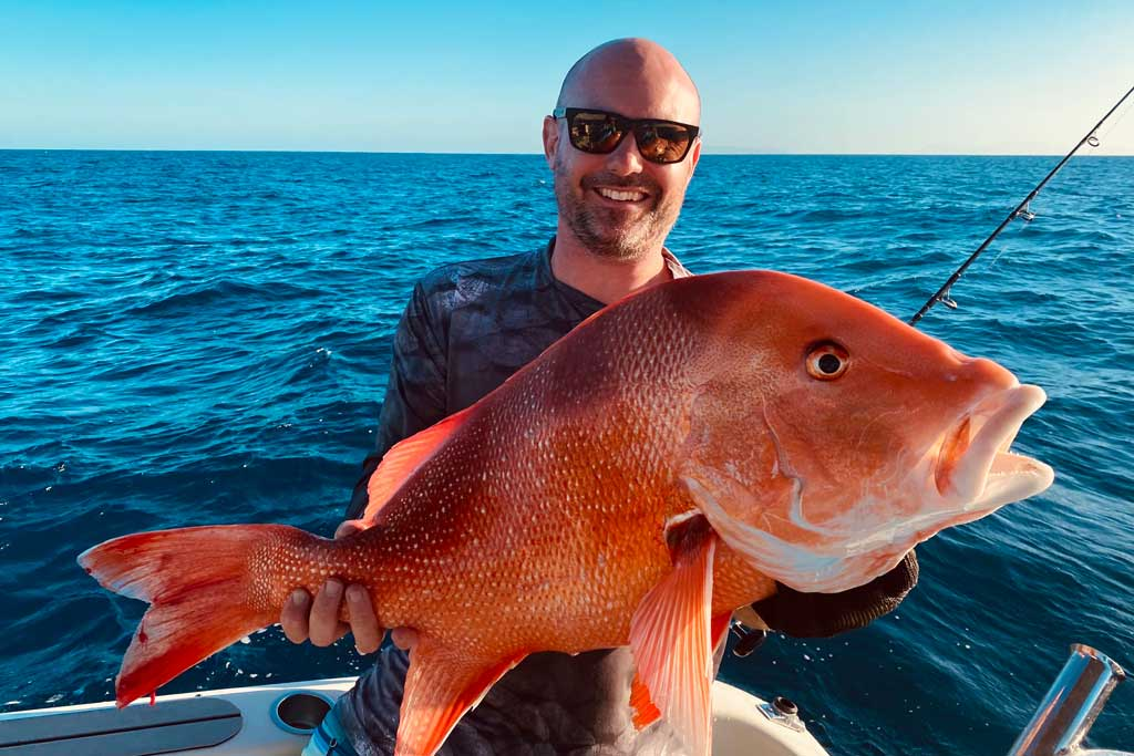 A smiling angler in sunglasses holding a Red Emperor Snapper, with blue skies and water in the background