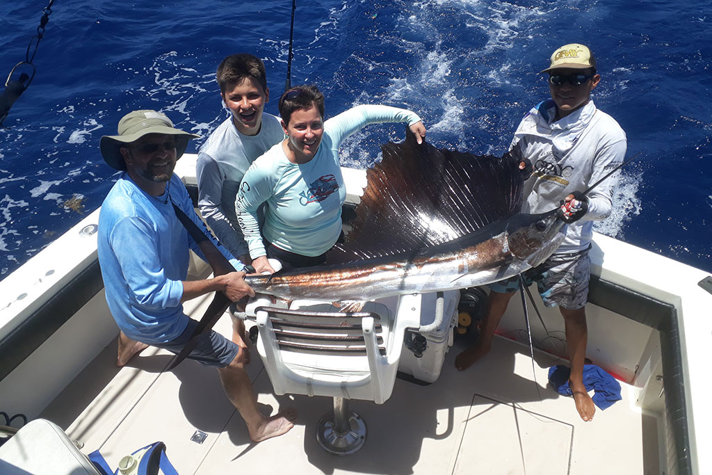 Four smiling anglers hold a large Sailfish caught fishing in Cancún