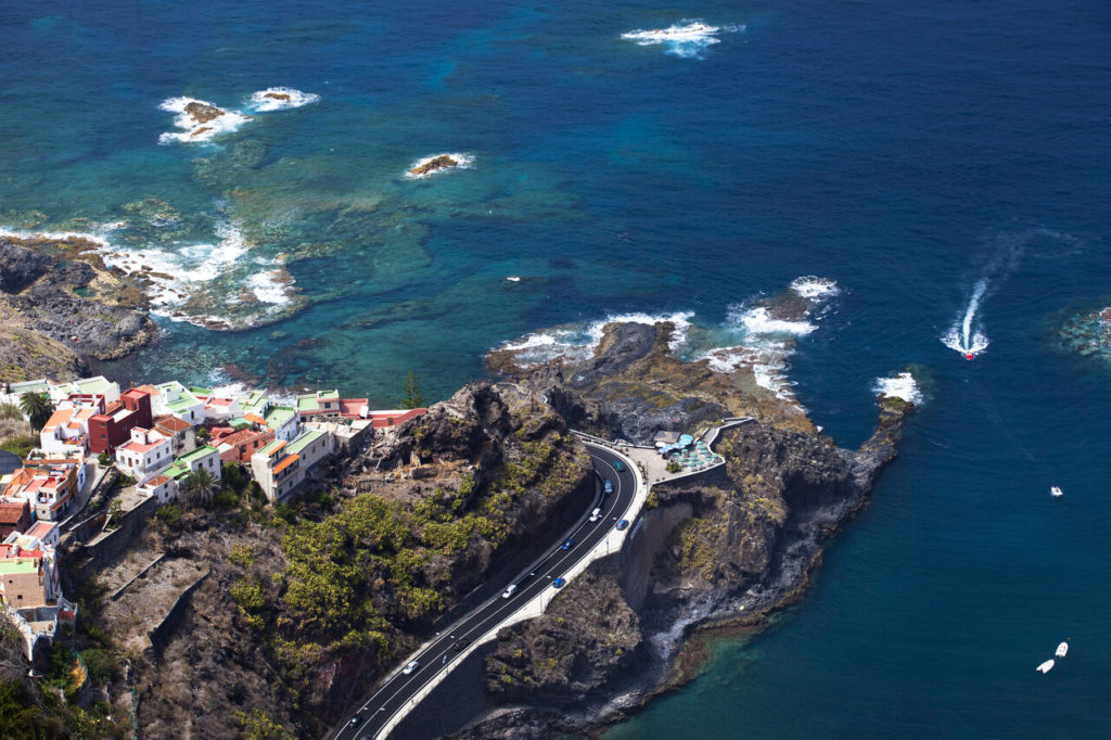 Aerial view of a rocky coast on Tenerife with a village on the left.