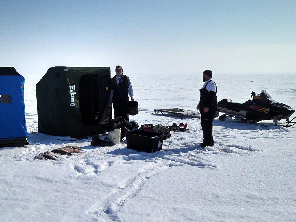 Two ice fishermen standing next to their gear and the fish they caught
