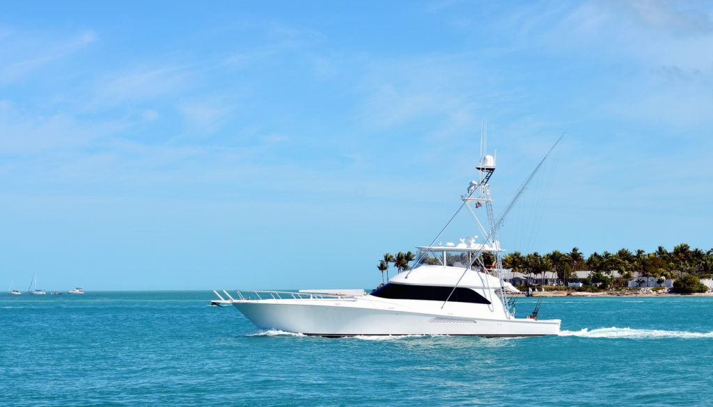 A white sport fishing boat leaving Sunset Key in Key West Harbor to go fishing in the Atlantic Ocean