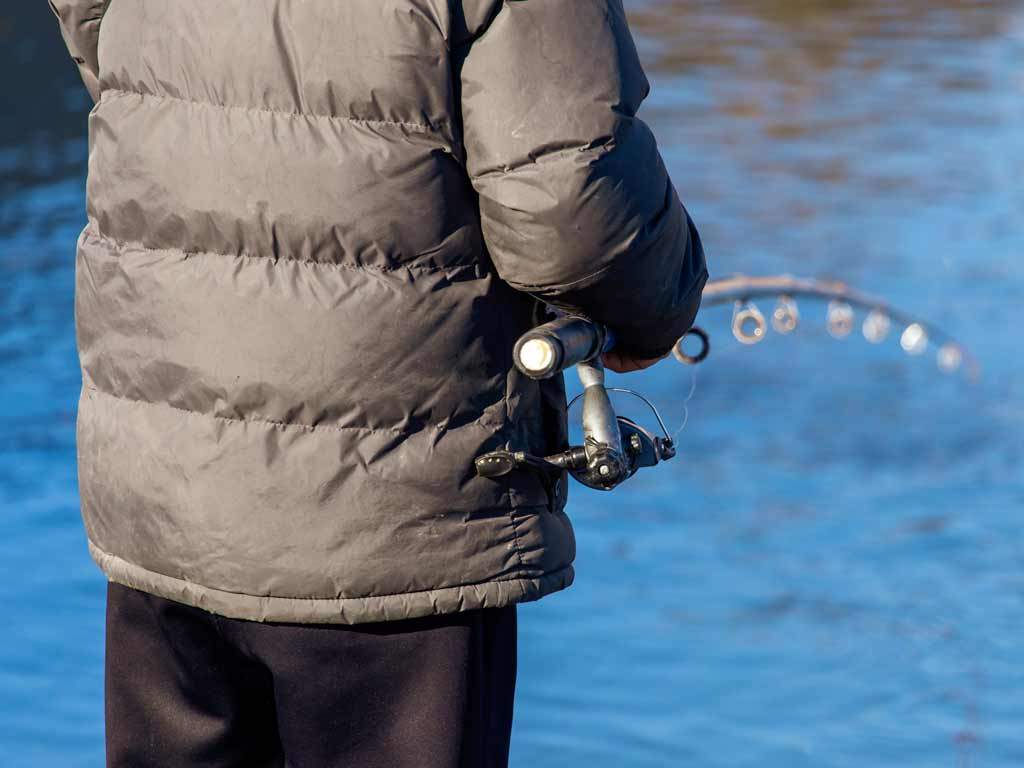A person in a windbreaker jacket caught from behind, holding a fishing rod