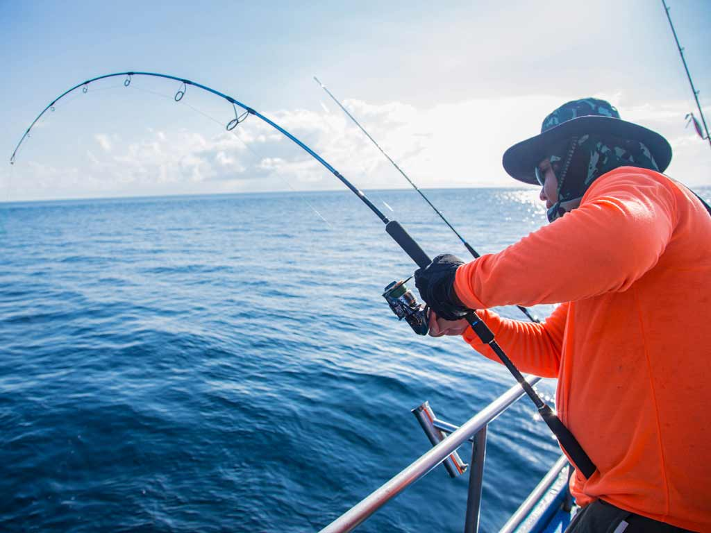 A deep sea fisherman in a hat reeling in his catch while standing close to the boat rail
