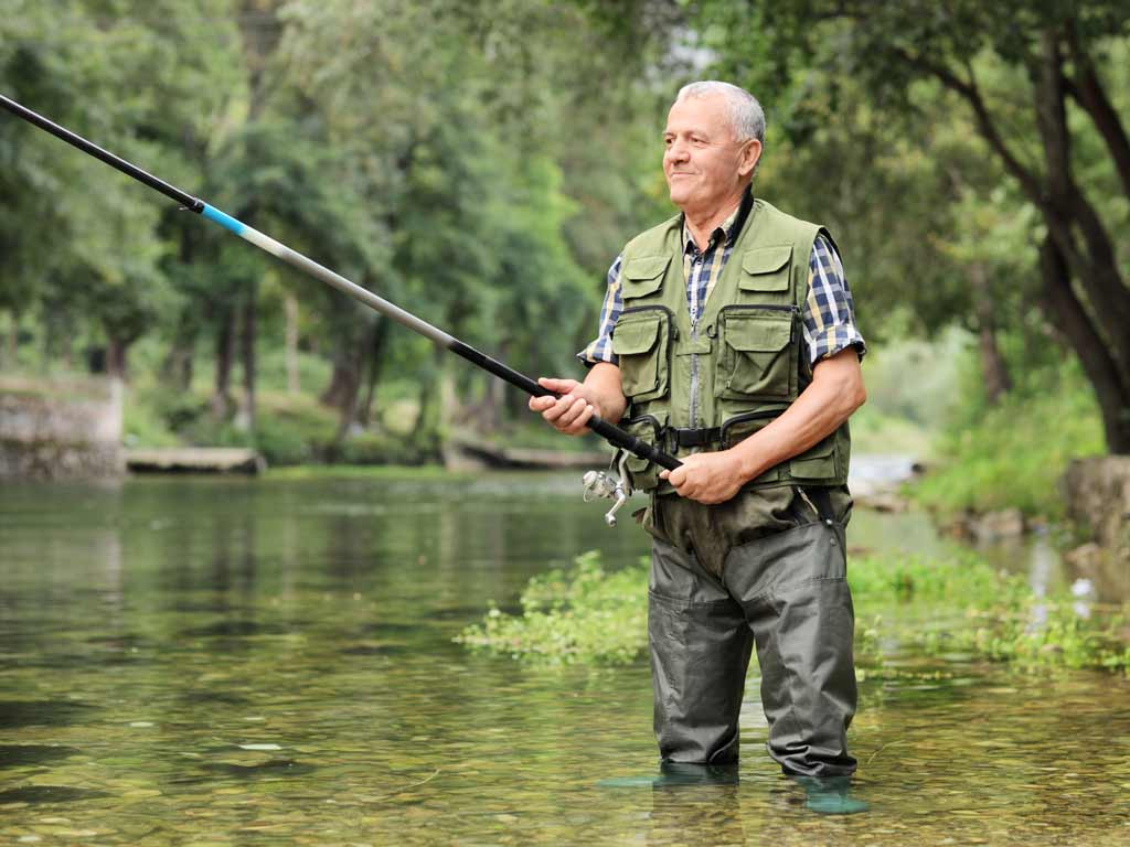 An elderly angler standing in a river holding a fishing rod