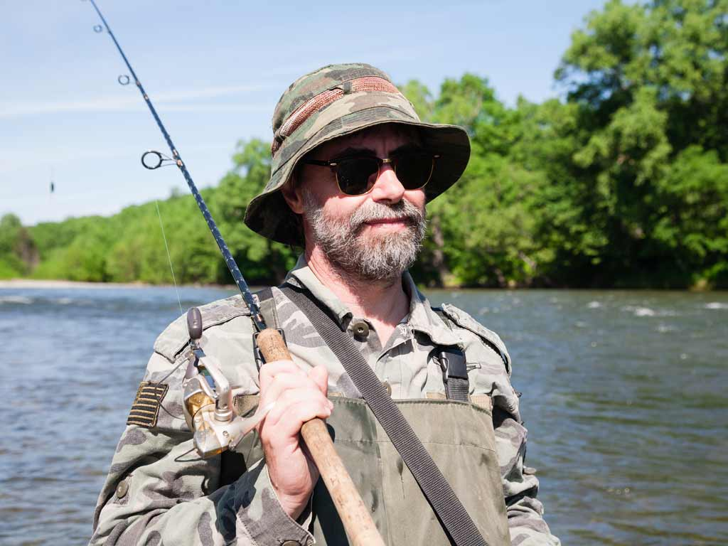 A fisherman in a hat and sunglasses hoding a fishing rod on his shoulder, with water and sky in the background