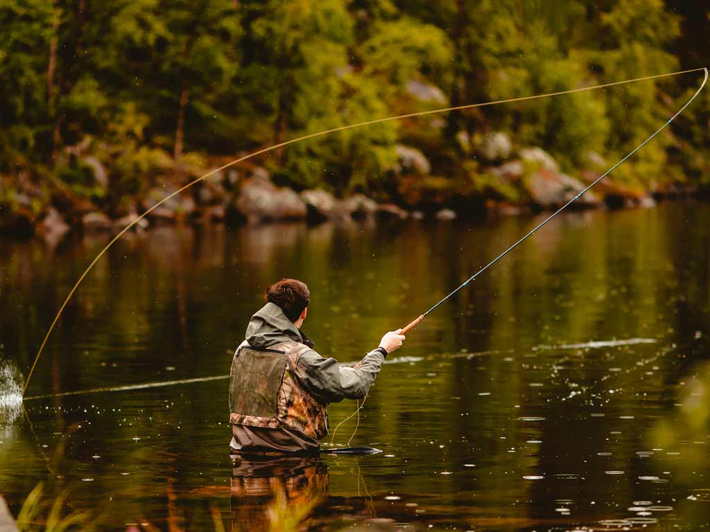 A fly fisherman standing waist-deep in a river, casting a fly