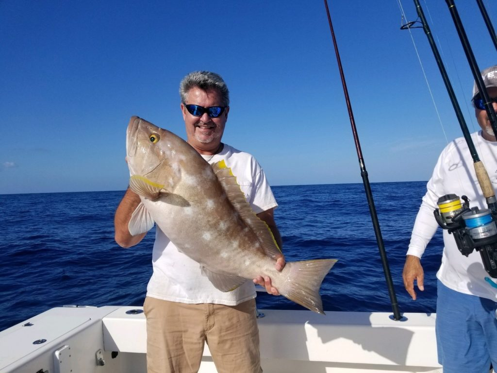 A smiling angler on a boat holding big Yellowedge Grouper