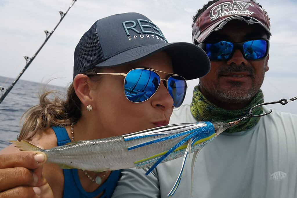 A man and a woman posing with a ballyhoo fishing bait rigged with a trolling header lure