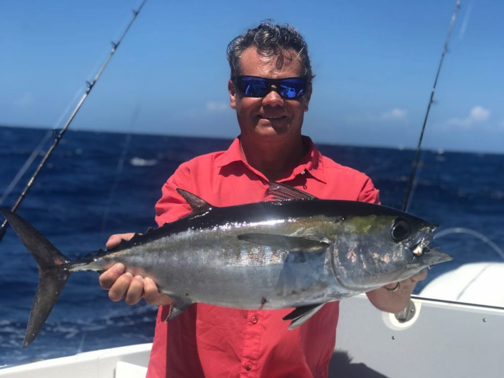 A smiling angler on a boat holding a freshly caught Tuna out of Marathon