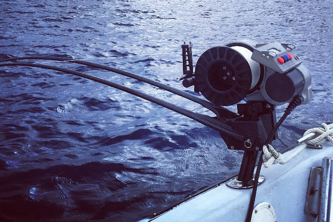 A deep-dropping rod hangs off the side of a fishing boat offshore from Cancún