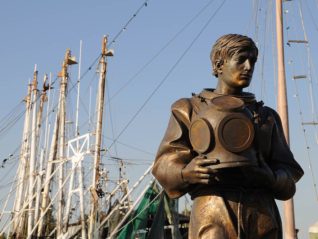 A statue of a sponge diver in Tarpon Springs, Florida, with docked boats in the background