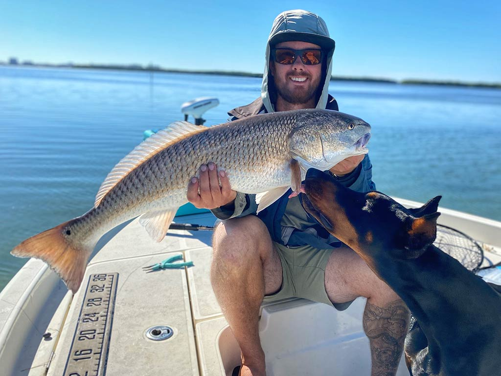 An angler sitting on a boat and holding a Redfish he caught while his dog curiously approaches it