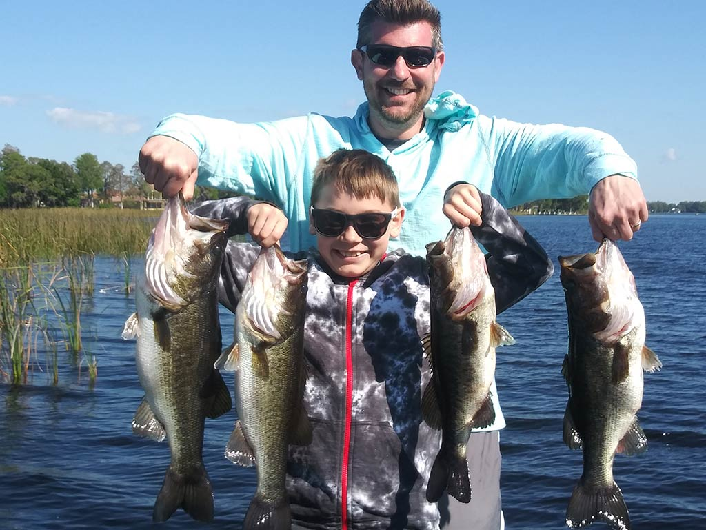 A father and son hold up the Largemouth Bass they caught on Lake Tarpon