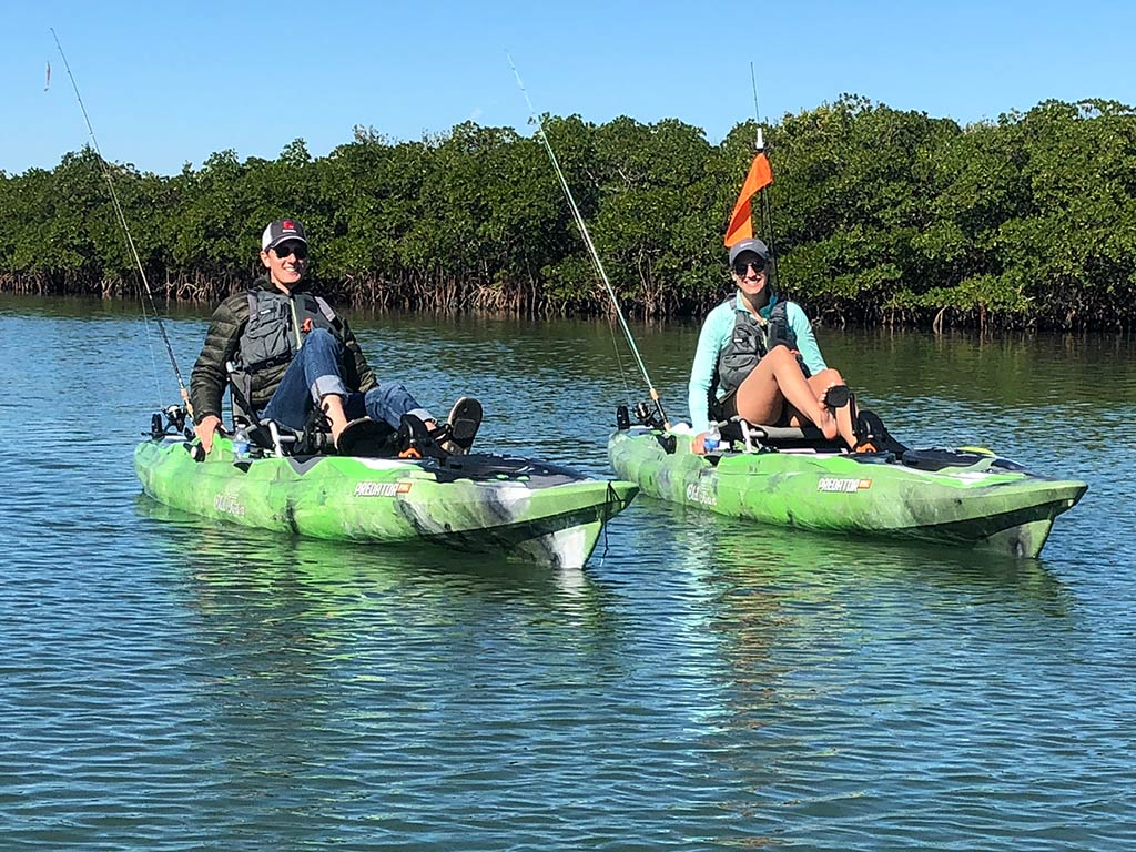 A pair of anglers paddling on their two green kayaks