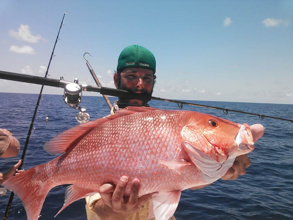 A tired angler holds up a Red Snapper he caught while holding onto his rod with his teeth