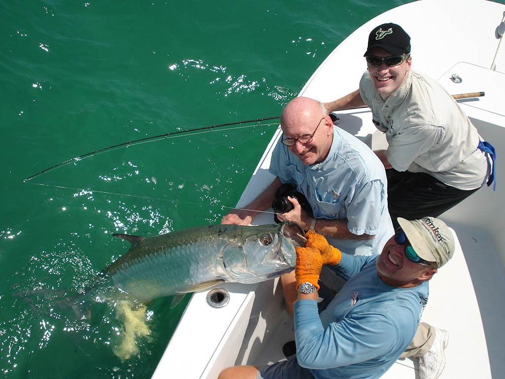 Three anglers smiling as they hold a large Tarpon they just reeled in